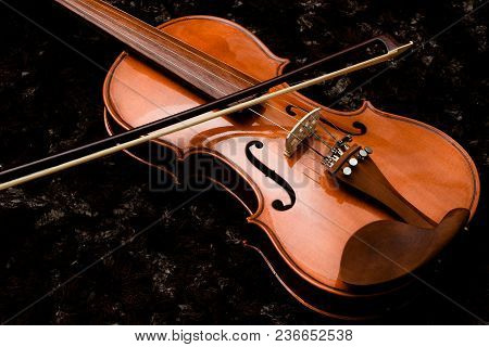 Classic Violin And Bow On A Dark Background Closeup