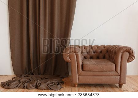 Classic Brown Textile Armchair In Interior With Curtain And Wooden Floor.