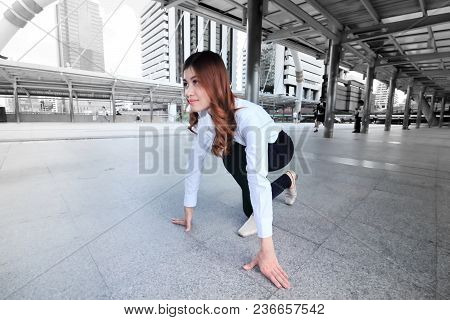Wide Angle Shot Of Attractive Young Asian Woman In Start Position Ready To Run At Urban City Backgro