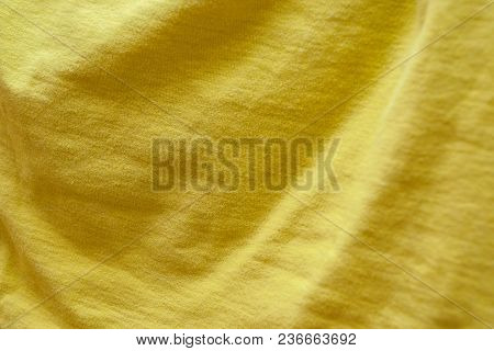 Hanging Fabric Of Mustard Color With Smooth Wavy Folds