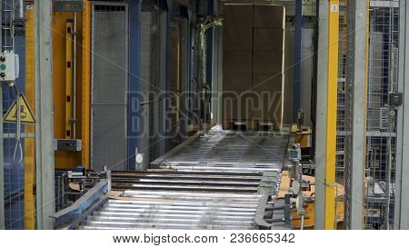 Shipping Box In Motion On Conveyor Belt, End Of The Line. Moving Conveyor Belt With Cardboard Boxes