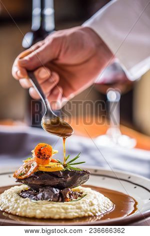 Chef In Pub Or Restaurant Decorates Portion Of The Meal In Pup Or Restaurant.