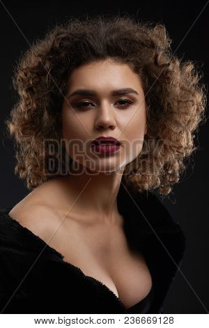 Sexy Curly Woman Posing In The Studio And Looking At Camera. Looking Beatiful And Passionate. Wearin