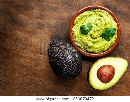 Avocado With Guacamole Sauce On A Dark Wood Background. Half And Whole Avocadoes Close Up. Top View.