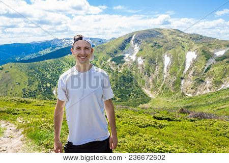 Man Hiker Relaxing On The Top Of Hill And Admiring Beautiful Mountain Valley View In Summer Day