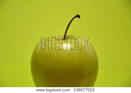 Healthy Diet Will Help You Lose Weight. Appetizing Green Apple On A Green Background