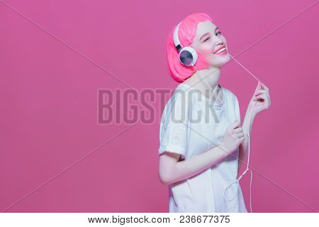 Trendy girl with pink hair enjoys the music on headphones. Pink background. Youth style, leisure.