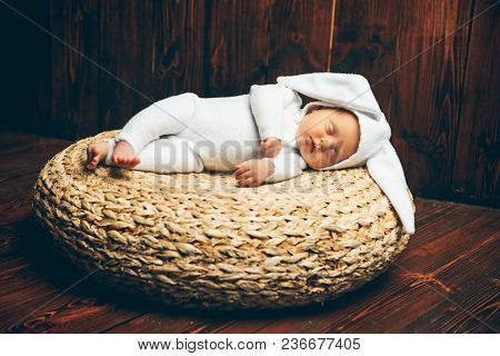 Cute newborn baby lies on a wooden background, dressed in rabbit costume. Easter holiday. Scenery in the rustic style.