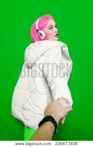 Trendy girl with pink hair wearing bright stylish clothes. Green background. Beauty, fashion, youth style.