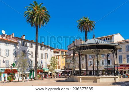 ANTIBES, FRANCE - SEPTEMBER 01, 2017: Bandstand on small town square among palms and houses in Old Town of Antibes - Mediterranean resort on Cote d'Azur in France, pupolar tourist destination.