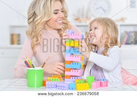 Portrait Of Mother With Little Daughter Making Figures With Constructor