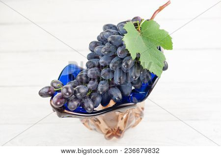 Bunch Of Fresh Ripe Blue Grapes With Green Leaf In Glass Vase On Old Wooden Rustic White Planks
