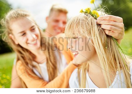 Mother decorates hair of her daughter with dandelion flowers in the summer