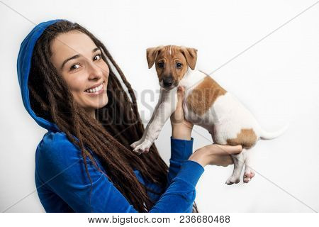 A Girl With Dreadlocks In Blue Clothes Is Holding Puppy Jack Russell Terrier Dog