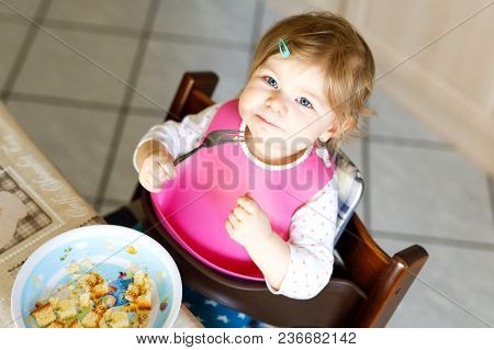 Adorable Baby Girl Eating From Spoon Mashed Vegetables And Puree. Food, Child, Feeding And Developme