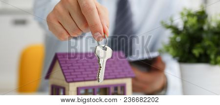 Male Hand Holds The Key To The Lock In The Hand Against The Backdrop Of The Toy House Sale Purchase