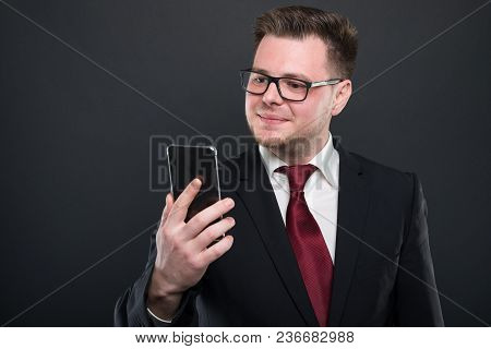 Business Young Man Looking At Black Smartphone.