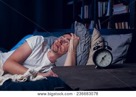 Photo of brunet with insomnia lying in bed with alarm clock