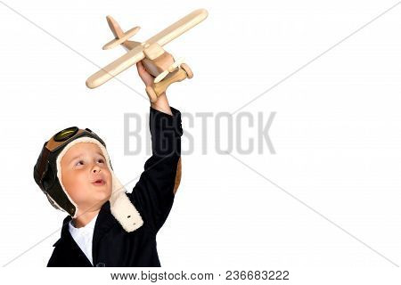 The Boy In The Helmet Of The Pilot Plays With A Toy Wooden Plane. He Dreams Of Becoming A Pilot. Con