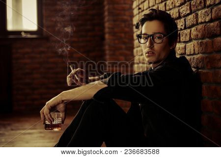 Attractive young man thoughtfully and calmly smoking a cigarette and drinking whiskey. Loft style interior. Men's beauty, fashion. Optics style.