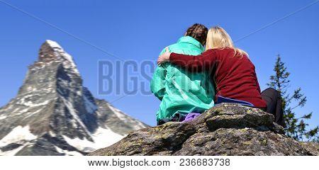 Two tourist sitting on the rock, in the background mountain Matterhorn - Pennine Alps, Switzerland