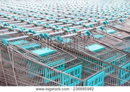 Red Shopping Cart. Trolley Pattern In Front Of A Supermarket, Ready For Customers To Use.