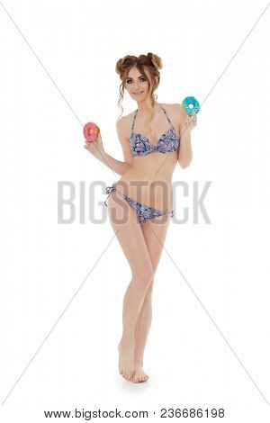 Cheerful young woman in bikini stands with donuts on a white background. Pin up style.