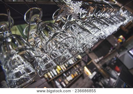 Glasses Hanging Over Bar Rack. Empty Glasses For Wine Above A Bar Rack