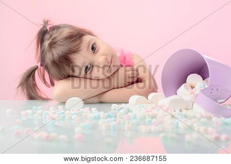 Portrait Of A Cute Little Girl With Marshmallow, Isolated Over Pink Background. Expressive Facial Ex