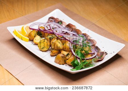 Restaurant dish - baked potatoes with onion rings and herring