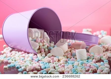 Violet Pail With Various Marshmallows On A Pink Background. Copy Space.