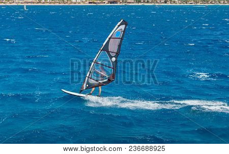 The Windsurfer On The Board Under Sail Moves At A Speed Along The Surface Of The Sea, Against The Ba
