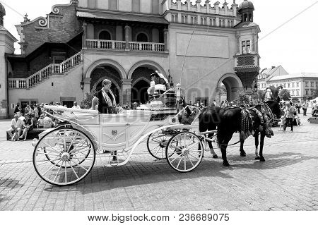 Krakow, Poland - June 04, 2016: Tourist Woman Sit In White Carriage With Black Horses In City Square