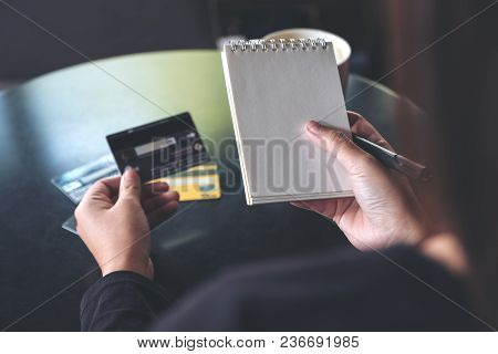 Closeup Image Of A Woman Holding A White Blank Notebook And Credit Cards On Table