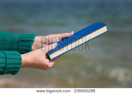 Close Up View Of Two White Female Hands Holding Thick Blue Book. Woman Reading At Sea Beach On Sprin