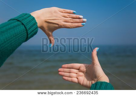 Close Up Of Female Caucasian Hands Isolated At Blue Sea And Sky Background. Young Woman Forms Frame