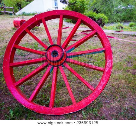 Wooden Red Wagon Wheel In A Field In El Calafate Argentina