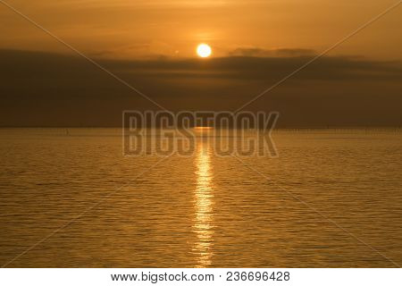 Orange View Of Gentle Sea Which A Sunbeam Reflected At Sunrise