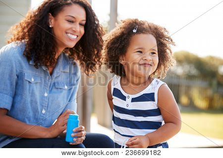 Young mixed race mother and daughter blowing bubbles outside