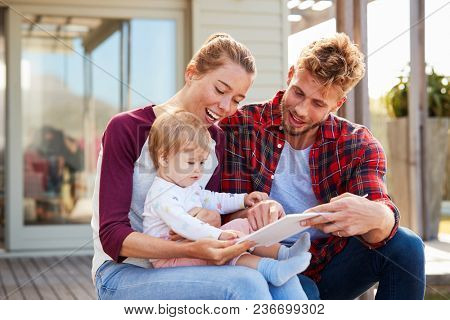 Young white family sitting and smiling at camera outside