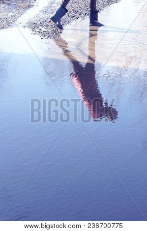 Reflection Of A Woman In Rubber Boots In A Large Puddle. Girl In Rubber Boots Is A Huge Puddle. The