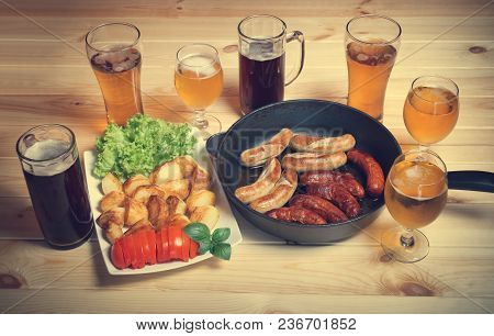 Beer, Grilled Sausages And Roasted Potato On Wooden Table