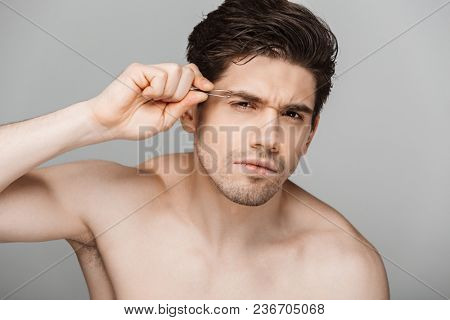 Close up beauty portrait of half naked concentrated young man using tweezers for his eyebrows isolated over gray background