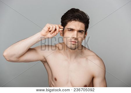 Beauty portrait of half naked focused young man using tweezers isolated over gray background