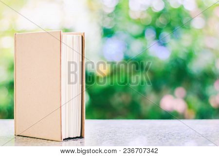 A Book Against Blurred Natural Green Background With Copy Space For Education And Learning Concept