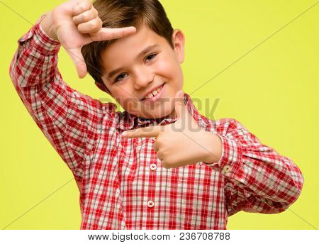 Handsome toddler child with green eyes confident and happy showing hands to camera, composing and framing gesture over yellow background