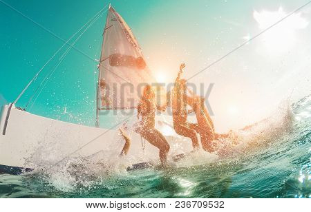 Happy Crazy Friends Diving From Sailing Boat Into The Sea - Young People Jumping Inside Ocean In Sum