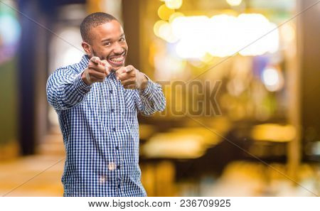 African american man with beard pointing to the front with finger at night
