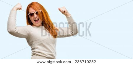 Beautiful young redhead woman happy and excited celebrating victory expressing big success, power, energy and positive emotions. Celebrates new job joyful isolated over blue background