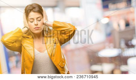 Beautiful young woman covering ears ignoring annoying loud noise, plugs ears to avoid hearing sound. Noisy music is a problem. at restaurant